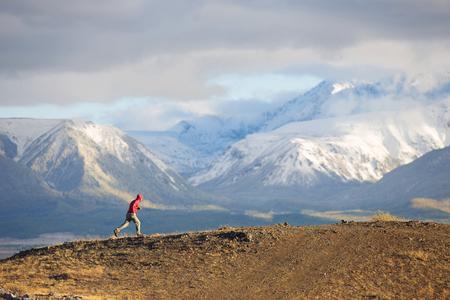Runner rugged mountain terrain. Man in red wear run crossing the mountain walley