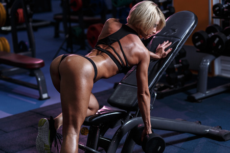 Sexy hot blonde fitness bikini girl with perfect shape body and butt workout with dumbbell in gym