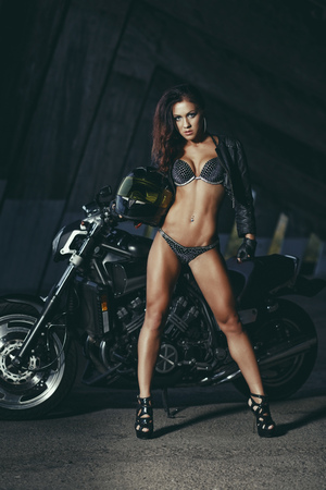 Sexy biker fitness girl with perfect slim body on black motorbike in leather wear posing in industrial place