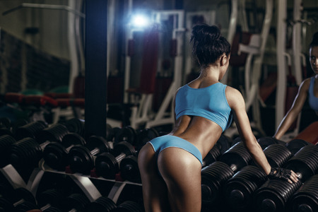 sexy young brunette woman resting in the gym and leaning on row of dumbbells in a blue sport wear