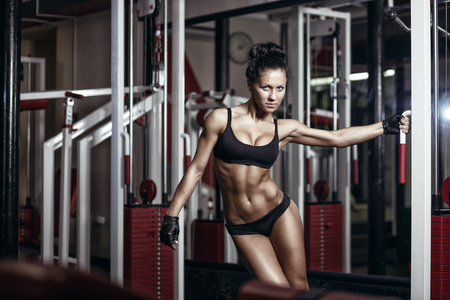 sport fitness: sexy young girl in the gym holding on training machine. Brunette fitness woman in black sport wear with perfect fitness body in gym Stock Photo