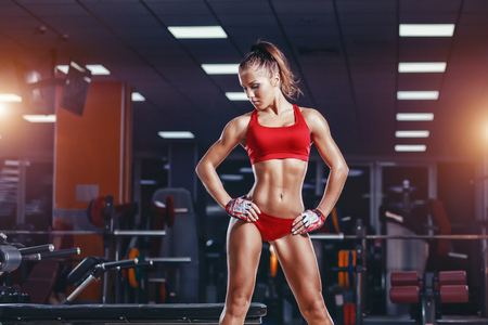 sexy young athletics girl resting after exercises. Fitness muscled woman in red sport clothing posing sitting on bench in gym