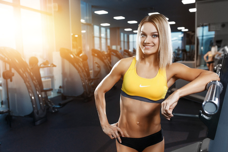 Sexy athletic sport smiling girl with perfect fitness body posing after sport workout training in the gym