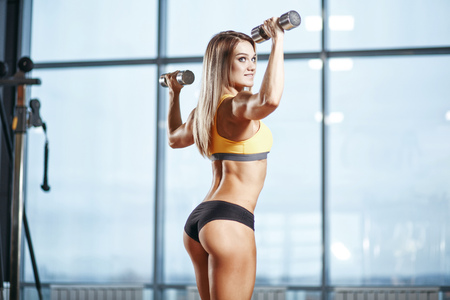 Sexy athletic sport smiling girl with perfect fitness body doing workout training with dumbbells in the gym