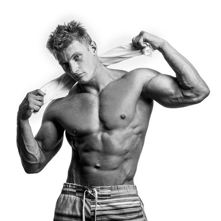 Young sexy man holding a towel isolated on white Banco de Imagens