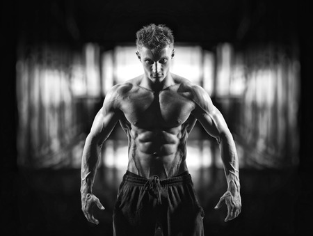 black and white photo of power athletic male fitness model in dressing room