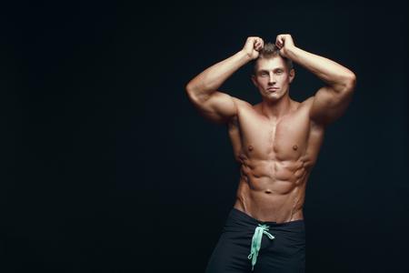 Portrait of a handsome muscular bodybuilder posing over black background. Banco de Imagens