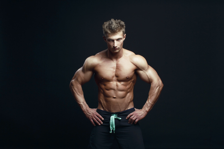 Portrait of a handsome muscular bodybuilder posing over black background. Stock Photo