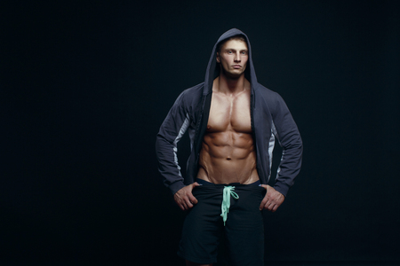 Portrait of a handsome muscular bodybuilder with muscular torso in hoodie posing over black background.