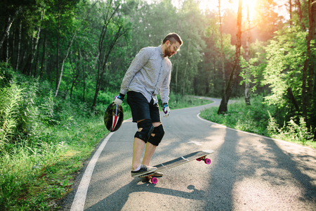 Man with longboard on road in nature park