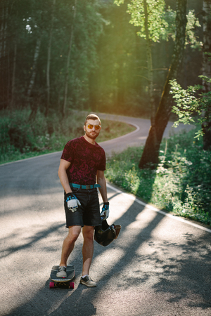 A skater with a board is standing on road in nature background. Young male wearing t-shirt and shorts