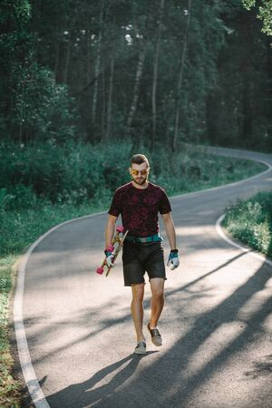 Young man with longboard on  road in the forest Banco de Imagens