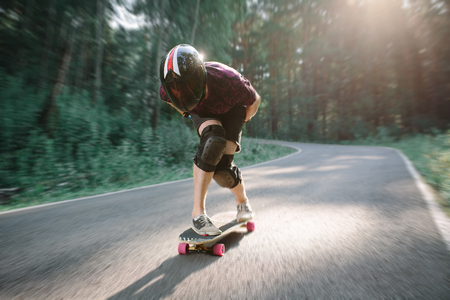 Skater boy in helmet on longboard rides on road in beauty nature