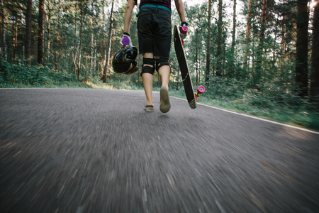 Young man with longboard is back on the road in the forest. Photos in motion