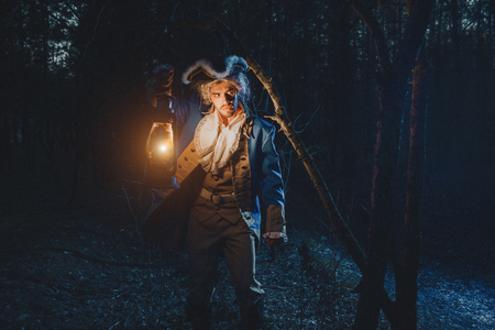 role model: Man dressed as a courtier or officer 17-18 age in night forest. Lighting his way with lantern
