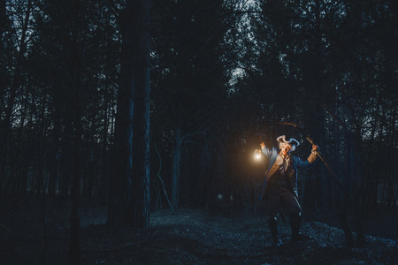 Man dressed as a courtier or officer 17-18 age in night forest. Lighting his way with lantern
