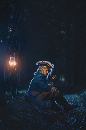 Man dressed as a courtier or officer 17-18 age in night forest. Sitting with old lamp on sidelines Banco de Imagens