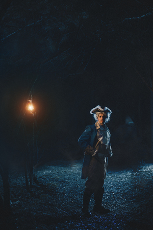 role model: Man dressed as a courtier or officer 17-18 age go under night forest lighting his way with lantern Stock Photo