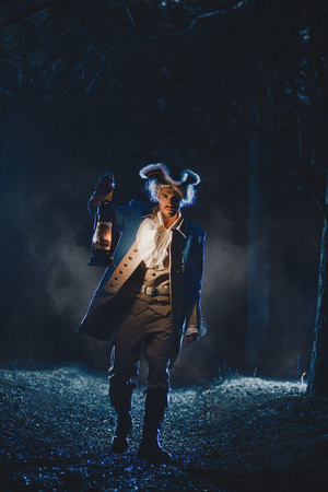 Man dressed as a courtier or officer 17-18 age go under night forest lighting his way with lantern Banco de Imagens