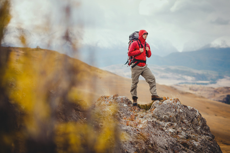 Adventure, travel, tourism, hike and people concept - man with backpack in mountain Banco de Imagens