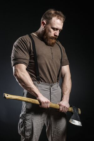 Lumberjack brutal bearded muscled man in brown shirt with suspenders on grey pants and axe on dark background 免版税图像 - 82666982