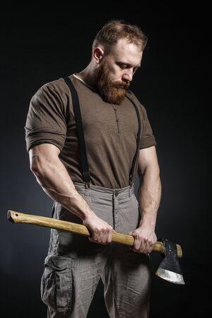 Lumberjack brutal homme musclé barbu en chemise marron avec des bretelles sur un pantalon gris et une hache sur fond sombre Banque d'images - 82666982