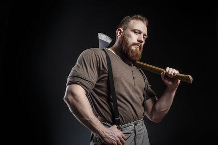 Lumberjack brutale bebaarde gespierde man in bruin shirt met hangers op grijze broek en bijl op donkere achtergrond