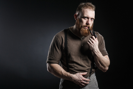 Lumberjack brutal bearded muscled man in brown shirt with smoking tube and suspenders on grey pants and axe on dark background Banco de Imagens