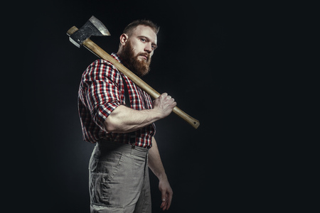 Lumberjack brutal bearded man in red checkered shirt with a smoking tube and axe on dark background Standard-Bild