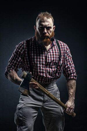 Lumberjack brutal bearded man in red checkered shirt with a smoking tube and ax on dark background