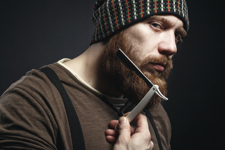 Lumberjack brutal bearded muscled man in brown shirt with shaving blade near his face  on dark background