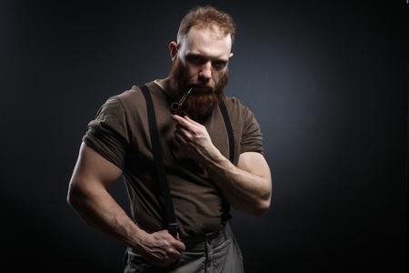 Lumberjack brutal red beard muscled man in brown shirt with smoking tube standing on dark background