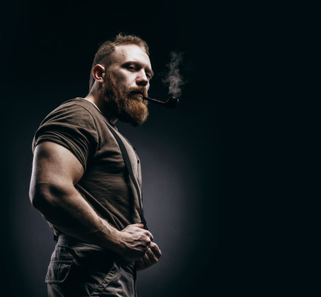 Lumberjack brutal red beard muscled man in brown shirt with smoking tube standing on dark background. Handsome man with red beard and moustache smoking pipe Stock Photo - 82667955