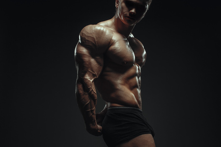 Handsome power bodybuilder showing his muscles isolated over black