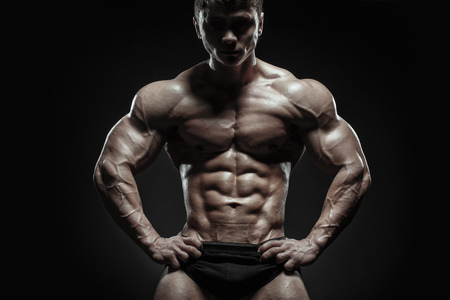 Muscular and fit bodybuilder fitness male model posing over black background. Fitness muscular body isolated