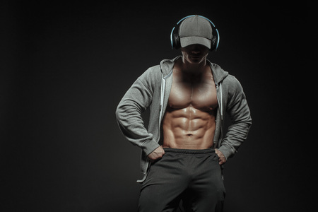 Unrecognizable fitness model athletic man shows strong muscles in grey hoodie, cup and headphones. Fitness muscular body isolated listen training music in headphones