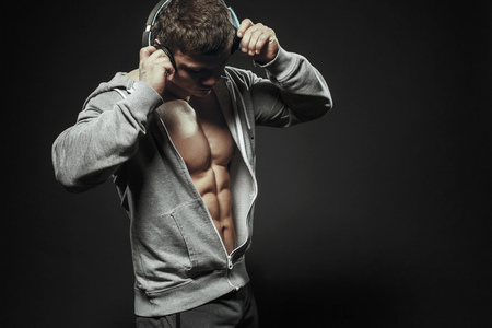Fitness model athletic man shows strong muscles in grey hoodie, cup and headphones. Fitness muscular body isolated listen training music in headphones Banco de Imagens