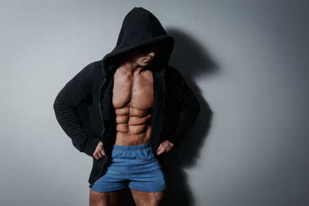 Athletic pumped male athlete in hoodie on gray background