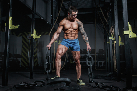 Athletic pumped man bodybuilder with chain in hall of crossfit