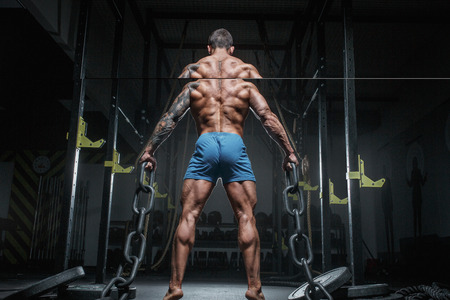 Athletic pumped man bodybuilder with chain in gym. Back view Banco de Imagens