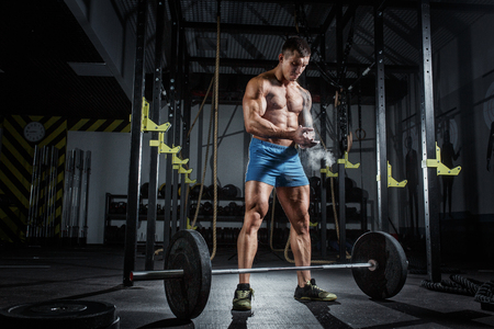Athletic pumped man bodybuilder stands in front of bar in gym
