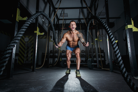 Athletic pumped man bodybuilder is engaged with ropes in hall of crossfit 写真素材
