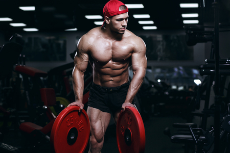 Muscular athletic bodybuilder fitness model posing and exercises in gym