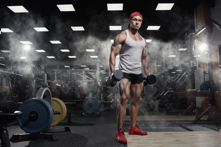 Athletic muscular bodybuilder with dumbbells  in gym