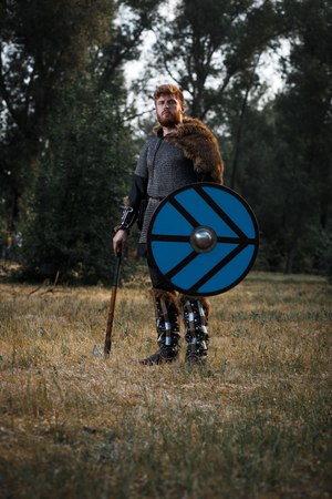 Warrior Viking in full arms with axe and shield in dark forest waiting for battle Banco de Imagens