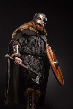 Warrior Viking in full arms with axe, shield and helmet on dark background