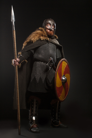 Warrior Viking in full arms with axe, shield and spear on dark background