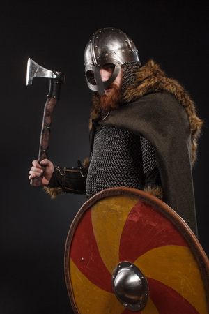 Warrior Viking in full arms with axe and shield on dark background Banco de Imagens