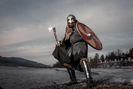 Guerrero vikingo escandinavo medieval en traje completo en la orilla del mar de invierno Foto de archivo