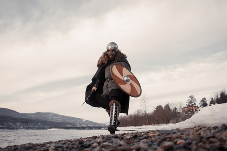 Medieval Scandinavian warrior Viking in full outfit on shore of winter sea 版權商用圖片